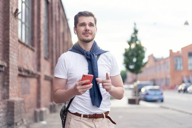 Bel homme souriant, écouter de la musique en marchant dans la ville