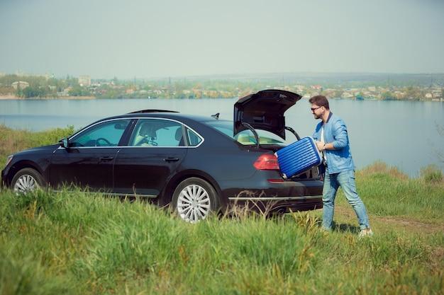 Bel homme souriant en jeans, veste et lunettes de soleil partant en vacances, chargeant sa valise dans le coffre de la voiture au bord de la rivière.