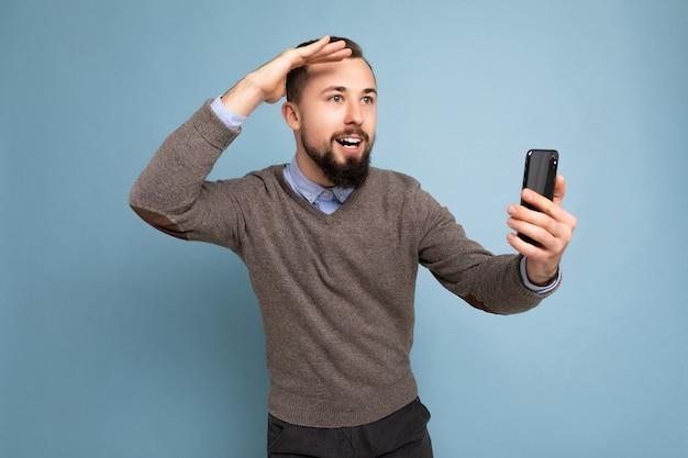 Bel homme souriant portant un pull gris et une chemise bleue tenant une carte de crédit à la recherche sur le côté