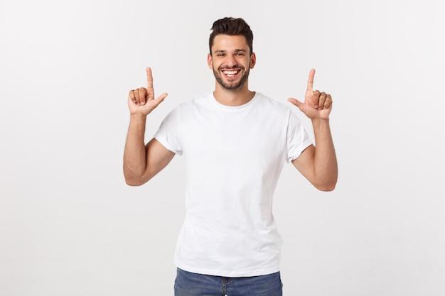Bel homme souriant en t-shirt blanc pointant vers le haut