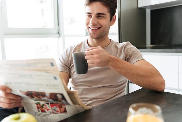 Bel homme souriant avec une tasse de thé lisant le journal dans la cuisine