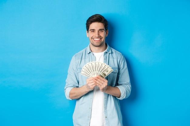 Bel homme souriant tenant de l'argent, concept de finance et de banque, debout sur un mur bleu