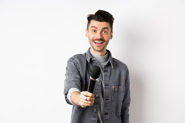 Bel homme souriant tendre la main avec microphone, vous donnant micro, debout sur fond blanc.