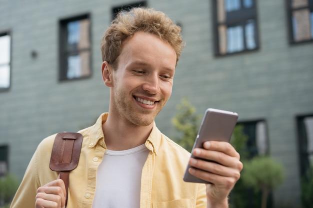 Bel homme souriant utilisant un téléphone portable faisant des achats en ligne en lisant de bonnes nouvelles dans la rue