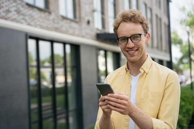 Bel homme souriant utilisant un téléphone portable faisant des achats en ligne