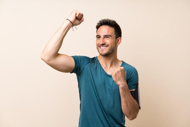 Bel homme sport sur fond isolé célébrant une victoire