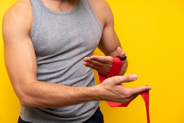 Bel homme sport sur mur isolé dans des bandages de boxe