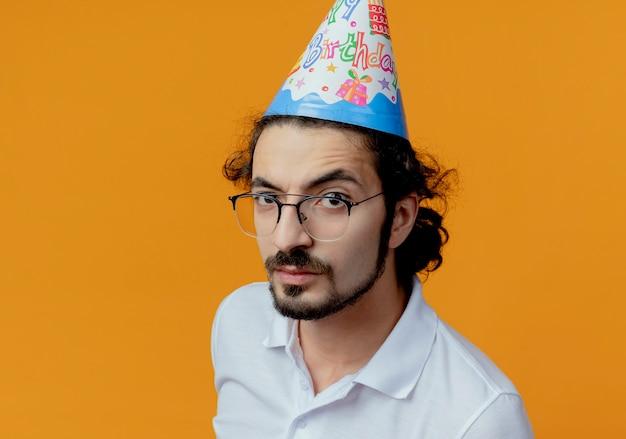 Bel homme strict portant des lunettes et une casquette d'anniversaire isolé sur orange