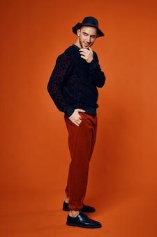 Bel homme en studio chapeau noir posant fond orange