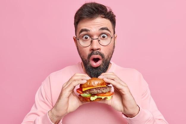 Un bel homme stupéfait pose avec un délicieux fast-food appétissant tient un délicieux hamburger porte des lunettes rondes un pull décontracté ne suit pas un régime aime tricher un repas habillé avec désinvolture