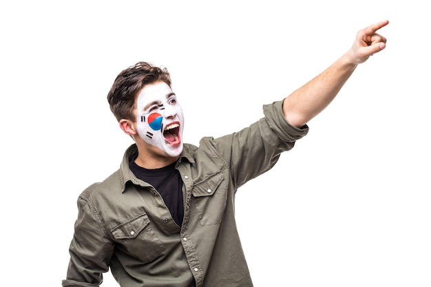Bel homme supporter fan de l'équipe nationale de la république de corée peint le visage du drapeau obtenir la victoire heureuse en criant la main pointue. émotions des fans.