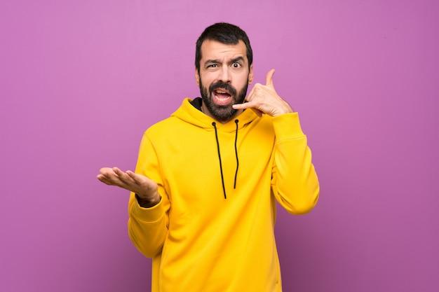 Bel homme avec un sweat-shirt jaune faisant un geste de téléphone et doutant