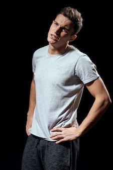 Bel homme en t-shirt blanc sur fond noir. vue recadrée.