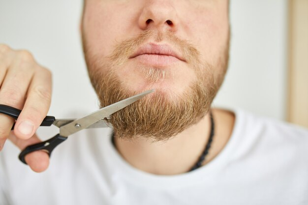 Bel homme en t-shirts blancs coupant sa barbe