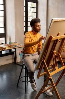 Bel homme talentueux assis devant sa peinture tout en travaillant dans son atelier