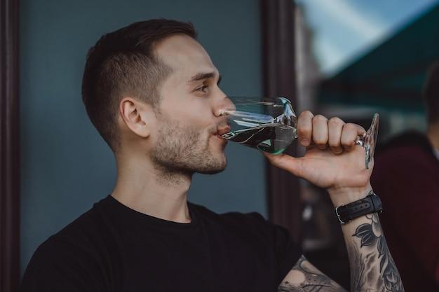 Le bel homme tatoué sur une terrasse d'été dans un café de la ville boit du vin. street cafe.