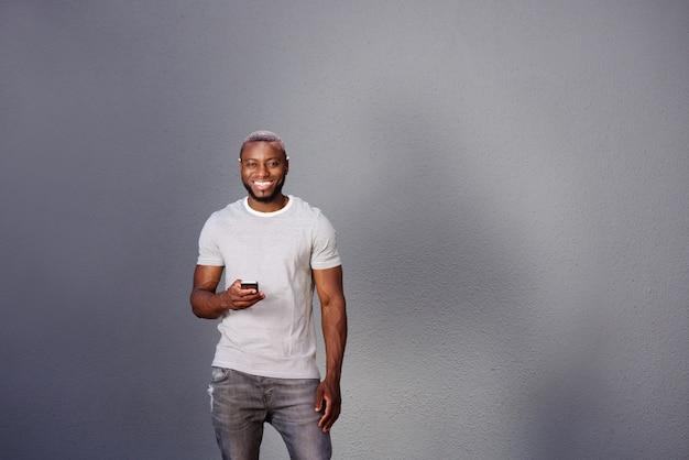 Bel homme avec un téléphone intelligent debout par un mur gris
