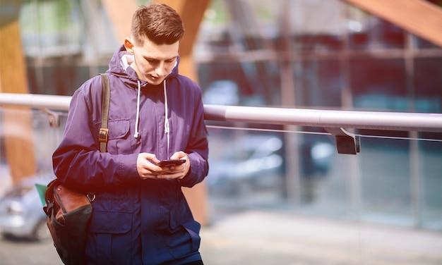 Bel homme téléphone portable appel sourire rue de la ville en plein air, jeune homme d'affaires séduisant chemise bleue décontractée parler
