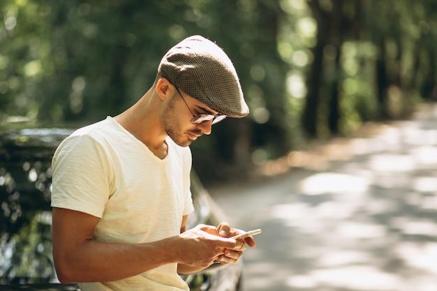 Bel homme avec téléphone en voiture
