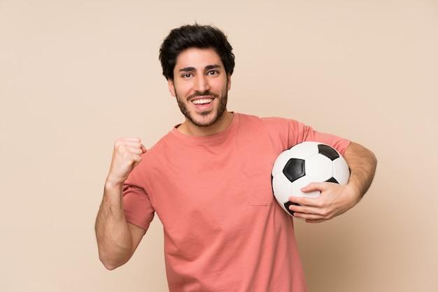 Bel homme tenant un ballon de foot