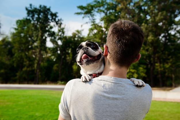 Bel homme tenant un bouledogue français, marchant dans le parc