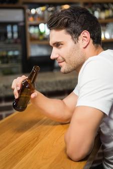 Bel homme tenant une bouteille de bière