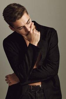 Bel homme tenant la main près de la chemise noire de visage posant un style moderne. photo de haute qualité