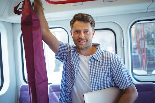 Bel homme tenant un ordinateur portable lors d'un voyage en train