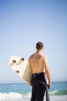 Bel homme tenant une planche de surf