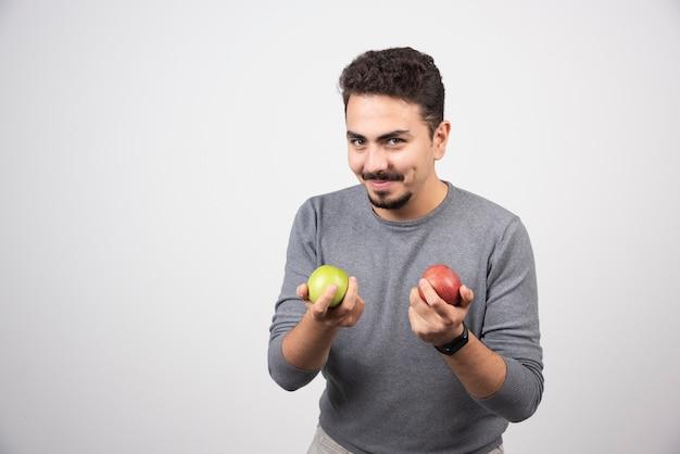 Bel homme tenant des pommes sur fond gris.