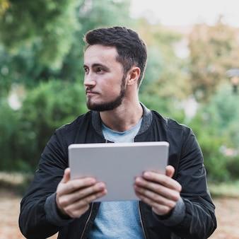 Bel homme tenant une tablette et regarder loin