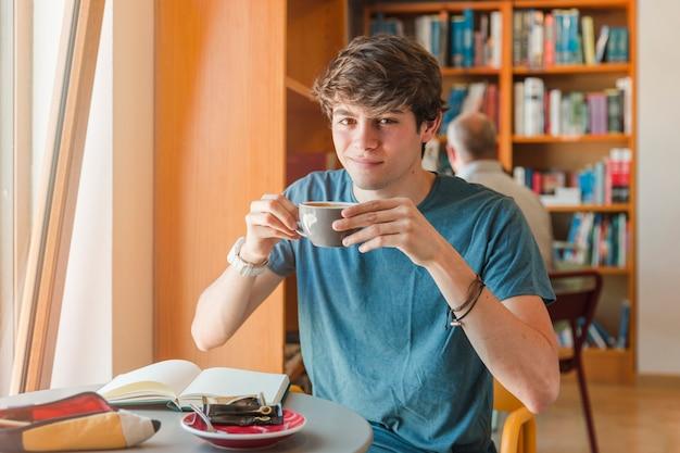 Bel homme tenant la tasse dans les mains
