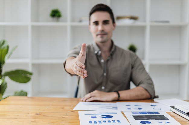 Un bel homme tend la main comme s'il demandait une poignée de main, un homme d'affaires étend la main en avant pour serrer un partenaire commercial, une poignée de main pour féliciter ou rendre hommage après une conversation d'affaires.