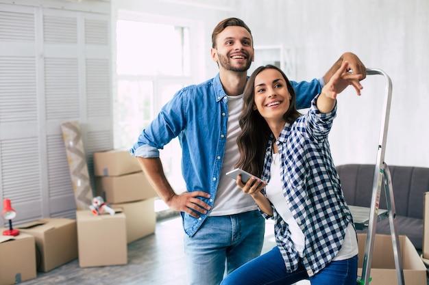 Un bel homme en tenue de denim vérifie quelque chose dans le smartphone avec sa magnifique épouse, s'appuyant sur l'échelle avec sa main gauche. concept de déménagement de maison