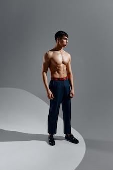 Un bel homme avec un torse nu en jeans et chaussures se dresse sur un fond gris