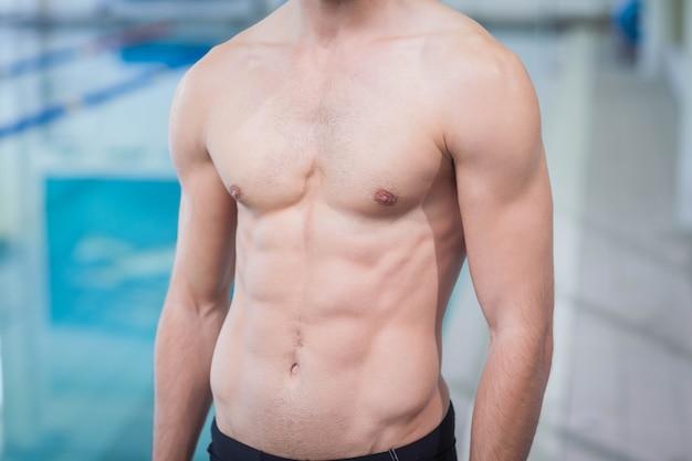 Bel homme torse nu à la piscine
