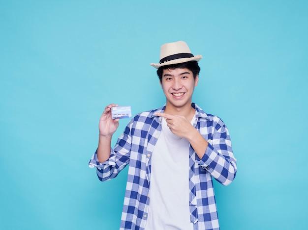 Bel homme de touriste avec carte de crédit sur un mur bleu clair. concept de voyage d'été