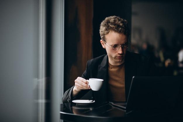 Bel homme travaillant sur un ordinateur dans un café et boire un café
