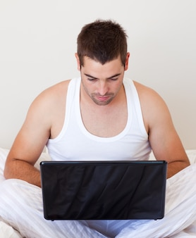Bel homme travaillant sur ordinateur portable à la maison