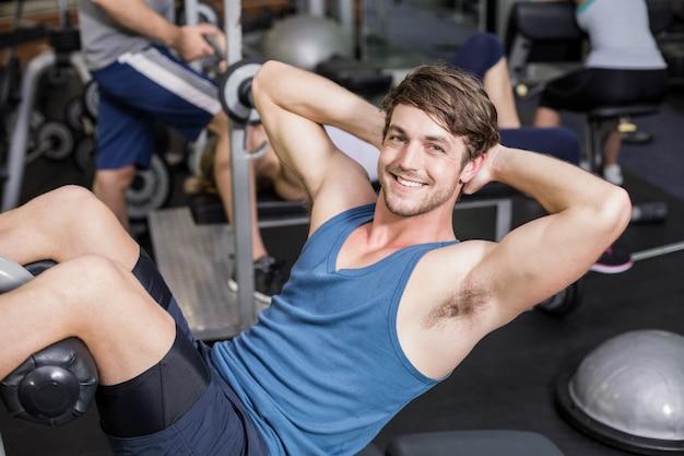 Bel homme travaillant ses abdos en salle de sport