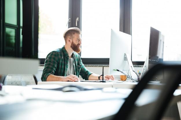 Bel homme travaille au bureau à l'aide d'un ordinateur.
