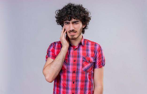 Un bel homme triste aux cheveux bouclés en chemise à carreaux se sentant mal
