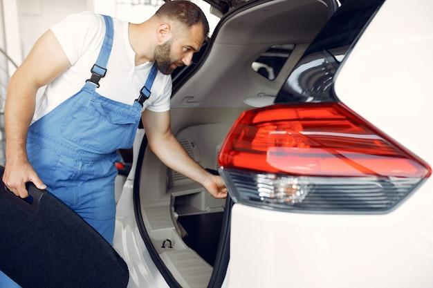 Bel homme en uniforme bleu vérifie la voiture