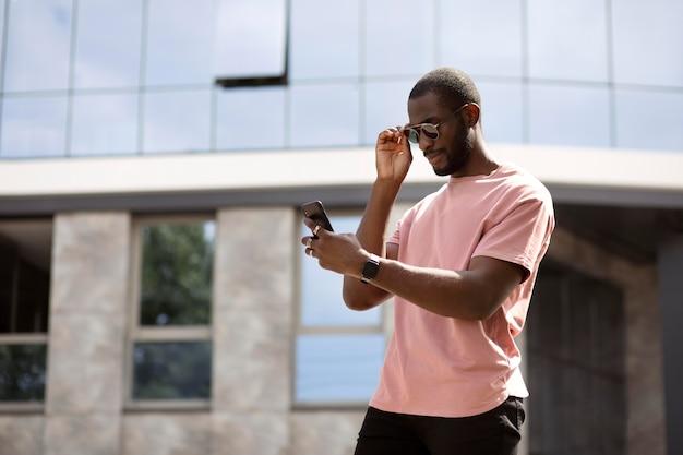 Bel homme utilisant un smartphone moderne à l'extérieur