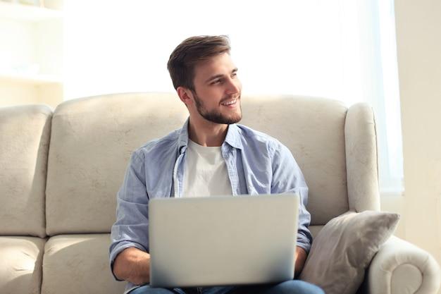 Bel homme utilise son ordinateur portable et sourit en se reposant sur un canapé à la maison.