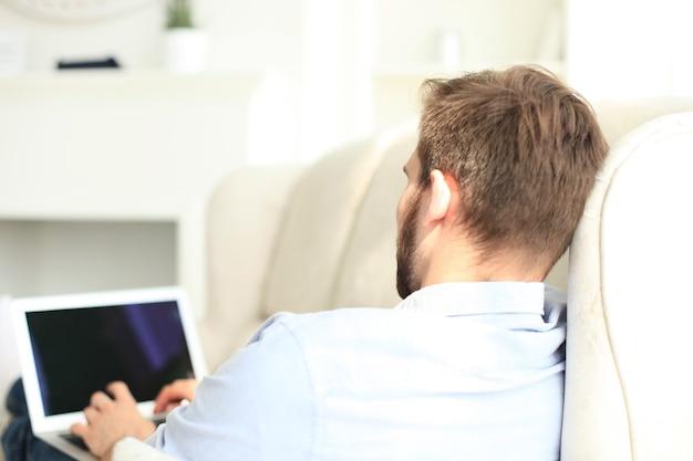 Bel homme utilise une tablette numérique et sourit en se reposant sur un canapé à la maison.