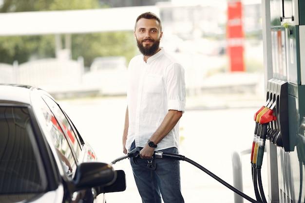 Bel homme verse de l'essence dans le réservoir d'une voiture