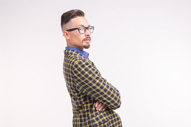 Bel homme en veste avec barbe et moustache dans des verres ayant les bras croisés, debout sur une surface blanche avec espace copie