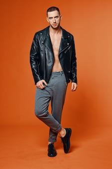 Bel homme en veste de cuir gonflé torse studio de mode fond isolé. photo de haute qualité