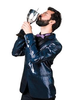 Bel homme avec une veste en paillette tenant un trophée
